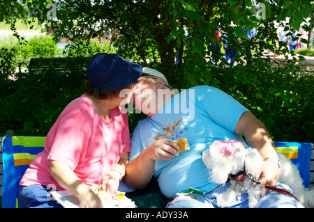 HUMOR Libertyville Illinois Older couple sit bench outdoors and kiss poodle interested in hot dog in mans hand - Stock Photo