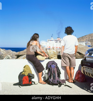 Young couple with backpacks awaiting a ferry at Kamares harbor on Sifnos in the Greek Islands Greece   KATHY DEWITT - Stock Photo