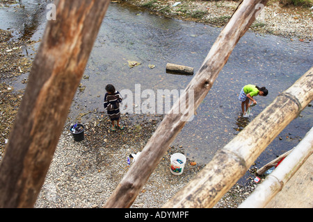 Two Girls Washing Clothes In River - Stock Photo