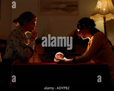 Fortune teller and client looking into crystal ball - Stock Photo