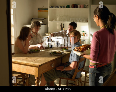 Two couples having lunch dinner in country cottage - Stock Photo