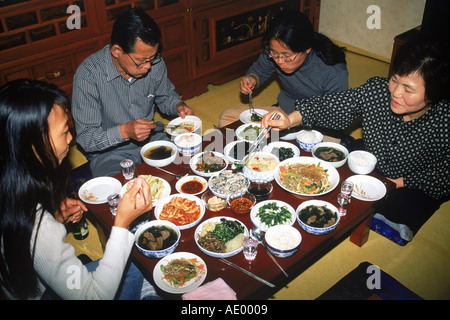 Family sitting at dinner table eating variety of home made Korean foods in South Korea - Stock Photo