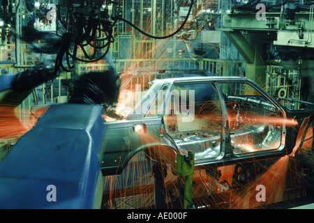 Sparks flying from spot welding robotics at automobile factory - Stock Photo