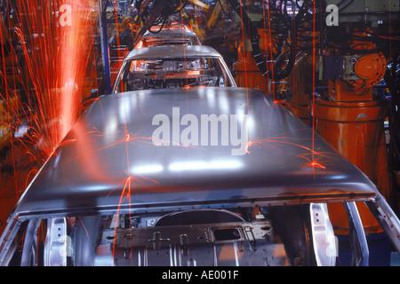 Sparks flying from spot welding robotics at Volvo Torslanda Plant in Sweden - Stock Photo