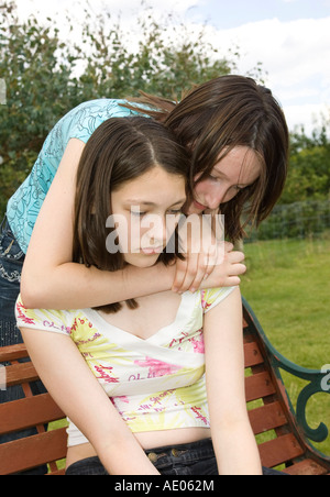 A girl comforting her best friend / sister - Stock Photo