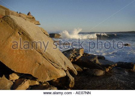 people watching surfer on big wave at Bondi Beach passing Ben Buckler rock - Stock Photo