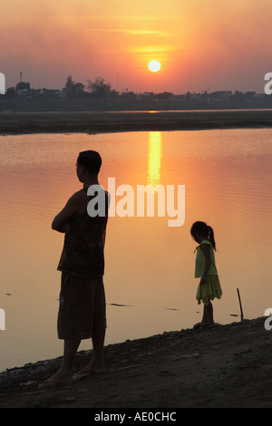 Man And Girl Standing Beside Mekong River At Sunset - Stock Photo