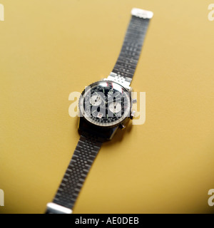 BREITLING SWISS CHRONOGRAPH WRIST WATCH WITH SELECTIVE FOCUS ON YELLOW BACKGROUND - Stock Photo