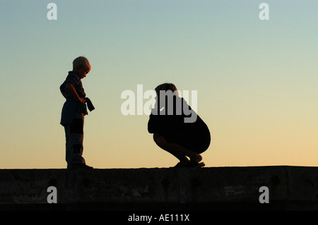 Silhouette of a mother and a child in the evening - Stock Photo