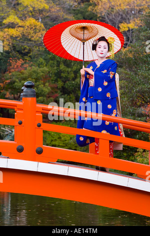 Asia, Japan, Honshu, Kansai Region, Kyoto, Geisha holding an ornate red paper umbrella - Stock Photo