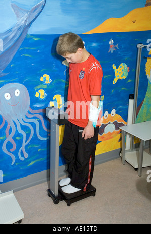 Young boy measuring weighing himself in hospital ward - Stock Photo