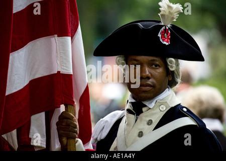 USA flag bearer in period military uniform (circa 1776) at the Edinburgh festival, Scotland. - Stock Photo