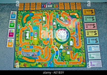 'The Game of Life' by Milton Bradley. The game board & all its' pieces, such as the money & cards, are all spread - Stock Photo