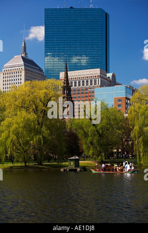 Swan boat in the lagoon at the Boston Public Garden with  several Back Bay buildings in the background Boston MA - Stock Photo