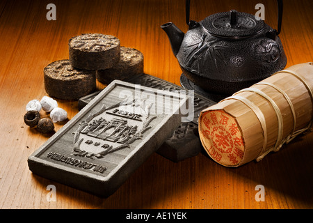 A tea kettle, tea bricks and tea rolls wrapped in fancy packaging placed on a table top.