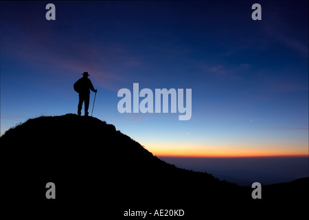 Achievement. A solitary climber on a peak in the Jura mountains, silhouetted against the dawn sky. - Stock Photo