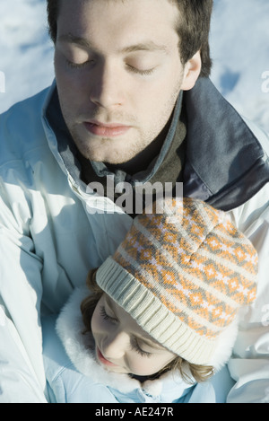Young man with girl in snow, eyes closed - Stock Photo
