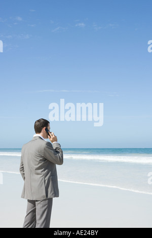 Businessman standing on beach, using cell phone - Stock Photo