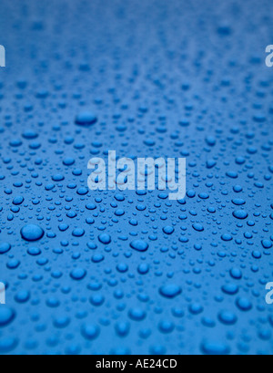 WATER DROPLETS ON BLUE METALLIC SURFACE - Stock Photo