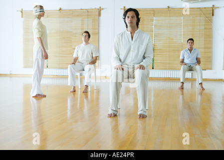 Group therapy, adults sitting in chairs while one woman stands wearing blindfold - Stock Photo