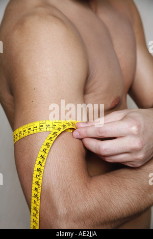 Man measuring his arm muscle - Stock Photo