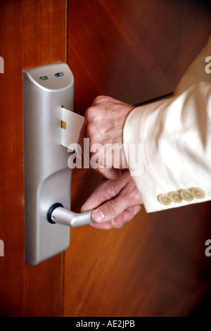 Man putting card key into hotel room door - Stock Photo