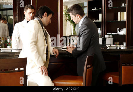 Two men at a bar paying the check - Stock Photo