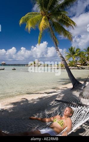 Girl resting in a hammock on the tropical island of Manihi in the Tuamotu Islands of French Polynesia