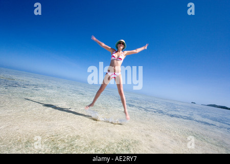 Girl in a bikini jumping for joy on a sandbank in a tropical lagoon in Fiji in the South Pacific - Stock Photo