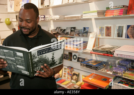 Ohio Cincinnati Contemporary Arts Center CAC Store Black male reads history picture book - Stock Photo