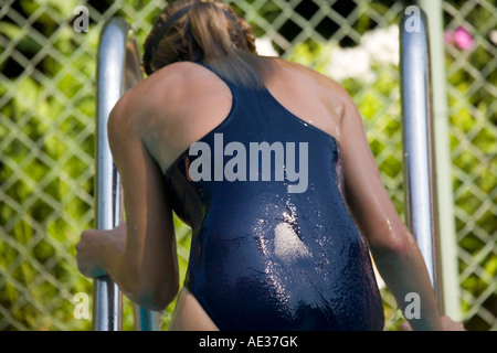 Caucasian female (13) climbing out of swimming pool - Stock Photo