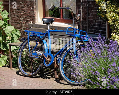 Bright blue Kronan bicycle parked against a house in Delft the Netherlands Design classic with cult  status