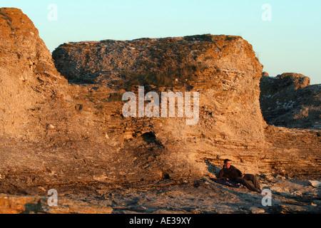 Man watching the sunset by the Rauks in Faro Gotland at Gamla Hamn - Stock Photo