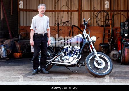 Harley Davison motorbike & Graham in front of garage - Stock Photo