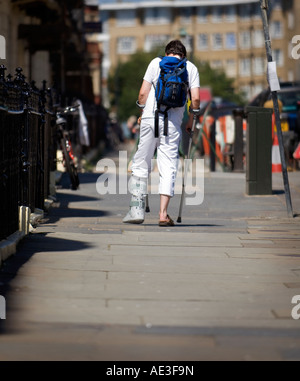 A young man with leg in plaster walking in the street. Picture by Jim Holden. - Stock Photo