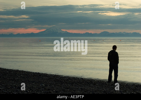 A beach of Cook Inlet, Alaska, sunset time with a silhouette of a guy standing next to the water - Stock Photo