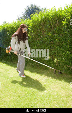 A woman using a petrol strimmer to trim rough grass in garden - Stock Photo