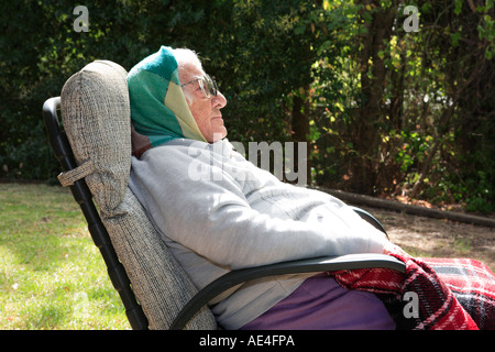 Elderly lady nineties, sitting outside resting in an armchair - Stock Photo