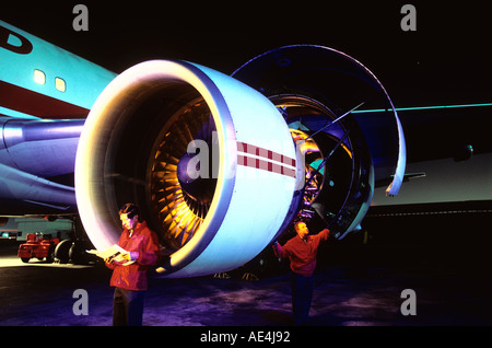 mechanics working on commercial airliner jet engine at night - Stock Photo