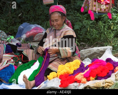 Woman sorts coloured yarns Bac Ha hilltribe market known for colourful Flower Hmong traders north Vietnam - Stock Photo