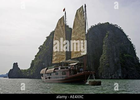 Large cruising junk moored off rocky island Halong Bay Vietnam - Stock Photo