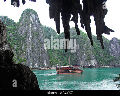 Rocks and stalactites in Hang Trong the Drum Grotto frame the Dragons Pearl cruising junk Halong Bay Vietnam - Stock Photo