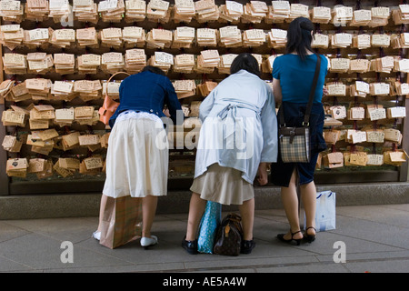 Women writing wishes and prayers on wooden votive plaques - ema - to hang on rack at the Meiji Jingu shrine in Tokyo - Stock Photo