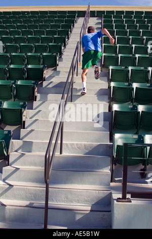 Man in his 20s running up the steep concrete steps of an aisle in an empty stadium getting a workout - Stock Photo