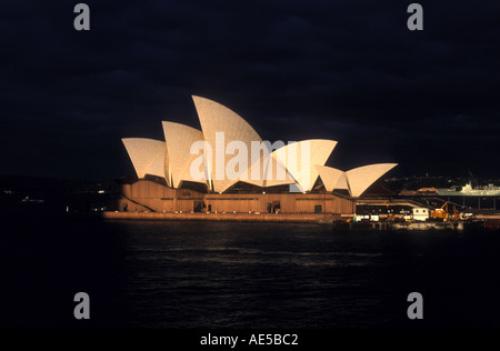 Sydneys Opera house glows in evening light against storm clouds 1649 - Stock Photo