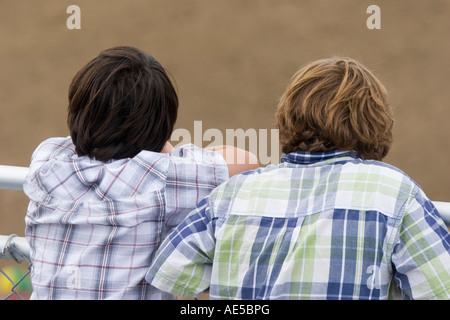 Two boys in plaid shirts leaning on a railing and watching a rodeo event - Stock Photo