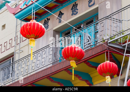 Bright red lanterns strung across San Francisco Chinatown street in front of colorful balcony with Chinese characters - Stock Photo