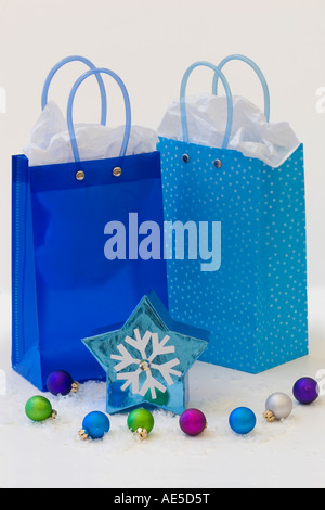 Three blue gift bags with tissue paper and snowflake star shaped three blue gift bags with tissue paper and snowflake star shaped box winter holiday gifts for negle Images