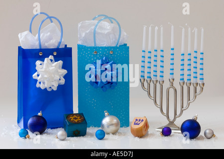 Display of Jewish Hanukkah items including gift bags menorah with candles dreidel gift box and ornaments - Stock Photo