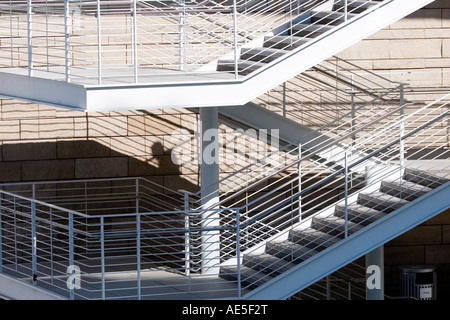 Shadow of torso and head cast on wall of exterior stairway with no man visible on the stairs - shows stealthiness - Stock Photo